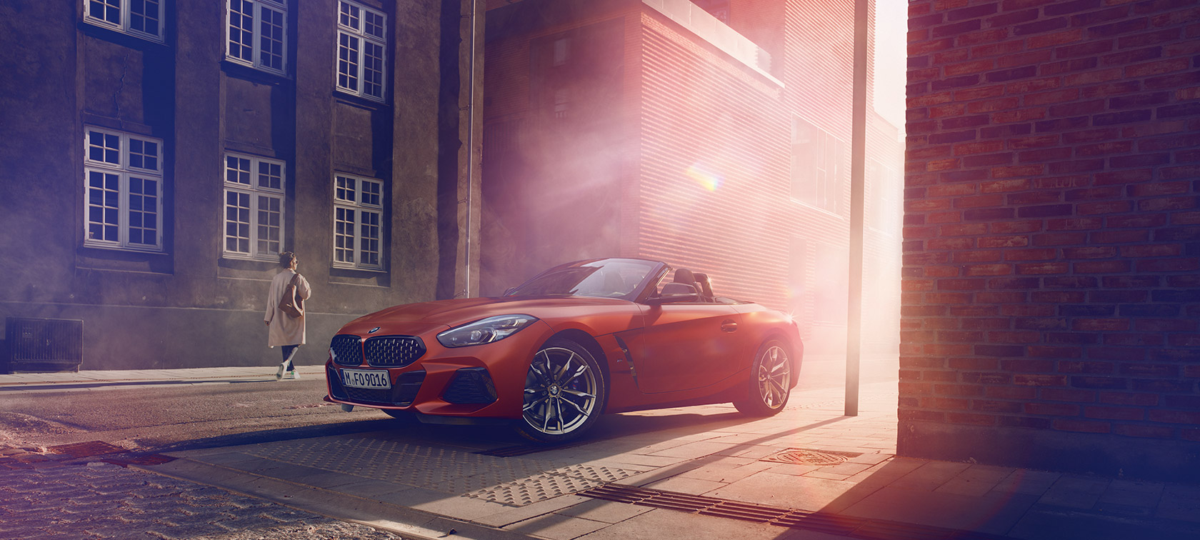 Orange BMW Z4 First Edition on half-light street in front of houses with women
