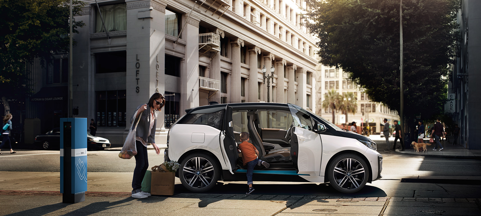 BMW range BMW i3 against an urban backdrop with woman and child